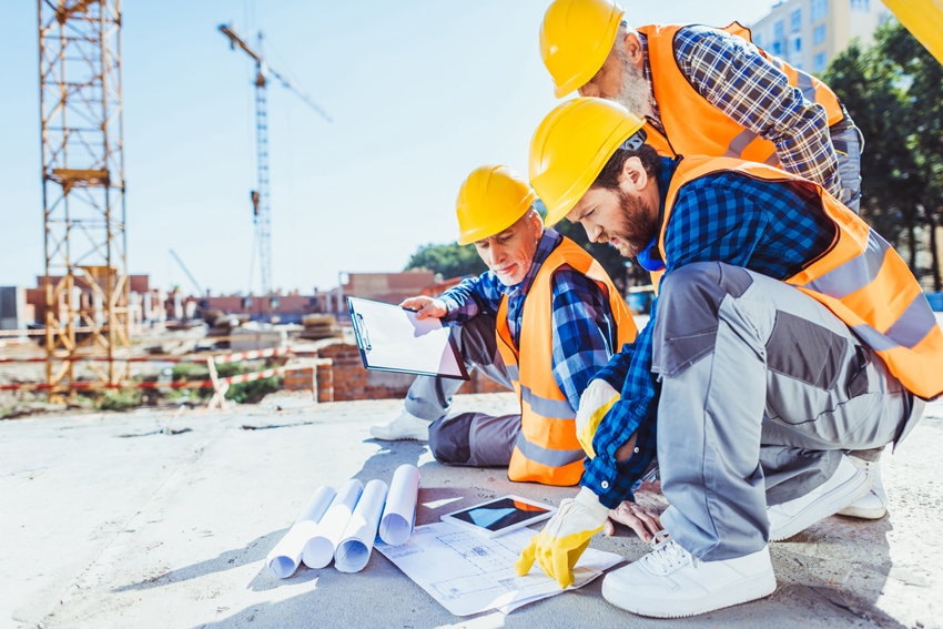 construction workers in uniform sitting on concrete at construct